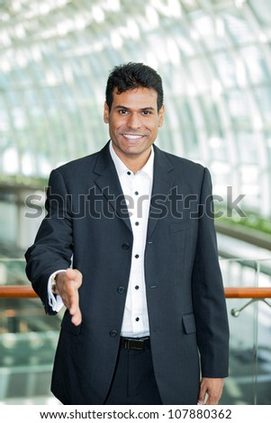 Happy Indian business man with his hand out ready to welcome you.