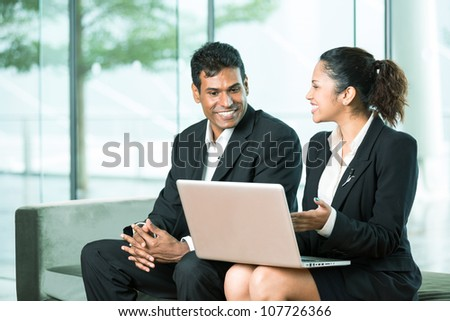 Happy Indian Business team working together around a laptop - stock photo