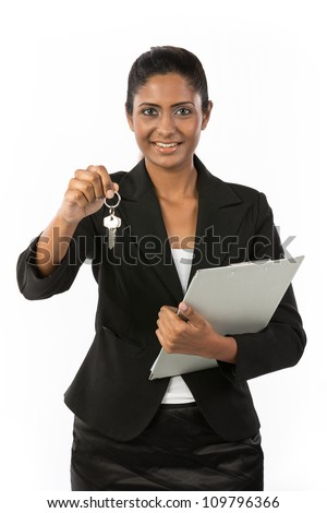 Happy Indian business woman or realtor showing keys. Isolated over white background. - stock photo