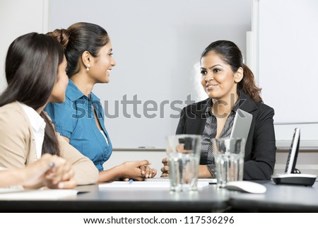 Happy Indian business woman sitting with her colleagues in a meeting