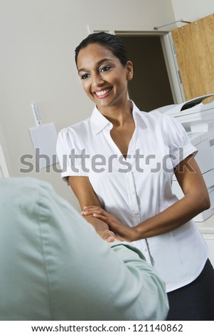 Happy Indian business woman welcoming coworker in office