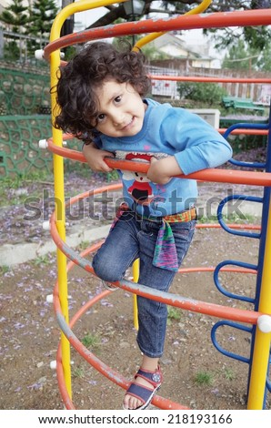 Happy Indian child enjoying the swing in playground. - stock photo