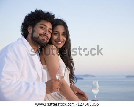 Happy indian couple sitting outdoors with champagne flutes and scenic background