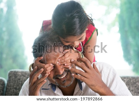 Happy Indian family at home. Asian girl surprising her father by covering daddy eyes. Parent and child indoor lifestyle. - stock photo