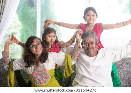 Happy Indian family at home. Asian parents playing with their kids, sitting on sofa. Parents and children indoor lifestyle.
