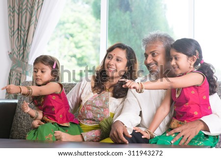 Happy Indian family at home. Asian people laughing and pointing to somewhere. Parents and children indoor lifestyle. - stock photo