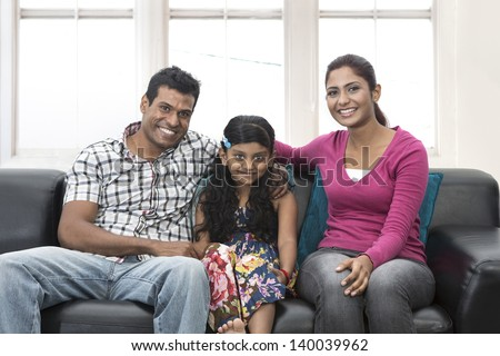 Happy Indian family at home with there child sitting on sofa. - stock photo