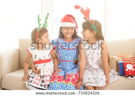 Happy Indian family celebrating Christmas holidays, with gift box and santa hat sitting on couch at home, adorable Asian children on festival mood.