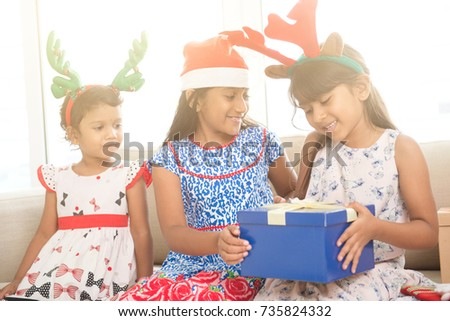 Happy Indian family celebrating Christmas holidays, with gift box and santa hat sitting on couch at home, joyful Asian children on festival mood.
