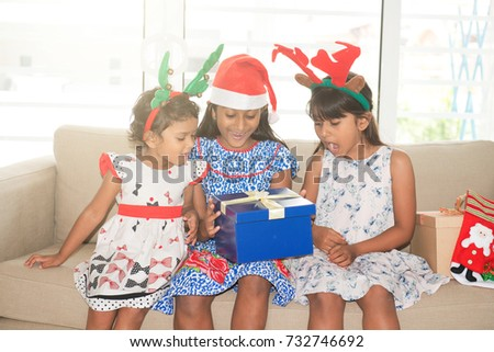 Happy Indian family celebrating Christmas holidays, with gift box and santa hat sitting on sofa or couch at home, joyful Asian children on festival mood.