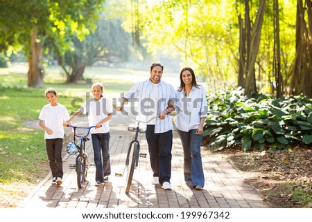 happy indian family of four walking outdoors in the park - stock photo