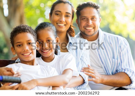 happy indian family outdoors looking at the camera - stock photo