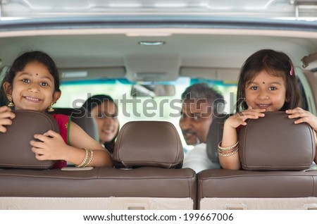 Happy Indian family sitting in car smiling, ready to vacation.  Asian parents and children. - stock photo