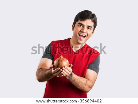 happy indian man holding piggy bank of money box made up of clay, clay money box & asian man, isolated over white background, indian man with piggy bank, money box, smiling, excited, happy, surprized - stock photo