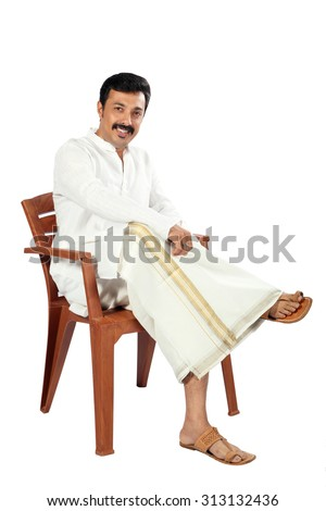 Happy Indian man sitting on the chair.He is using traditional dress called juba. - stock photo