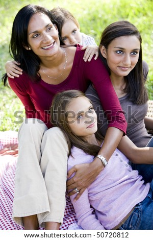Happy Indian mother with three beautiful mixed-race children sitting together outdoors - stock photo
