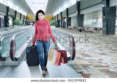 Happy indian woman wearing winter clothes and walking in the airport hall while carrying suitcase and shopping bags - stock photo