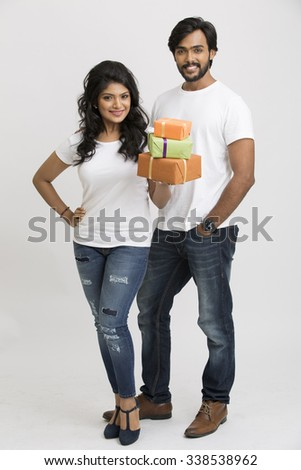Happy Indian young man and woman carrying gift boxes on white background. - stock photo