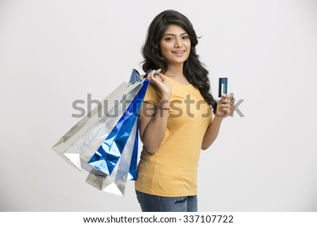 Happy Indian young woman with shopping bags and credit card - stock photo