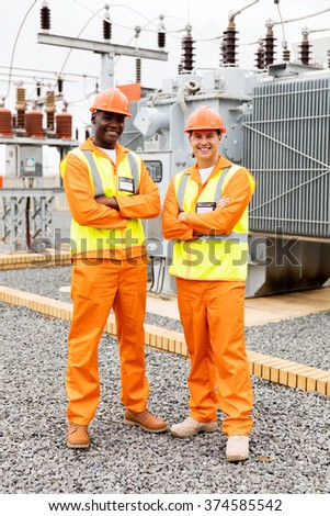 happy industrial engineers with arms crossed in substation - stock photo