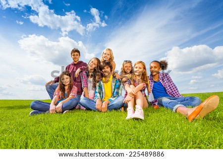 Happy international children sit on green meadow