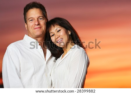 Happy interracial couple at sunset - stock photo