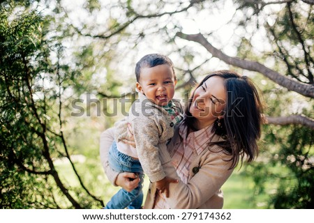 Happy interracial family. Caucasian mother and her african american son having fun in park - stock photo