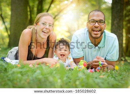 Happy interracial family is enjoying a day in the park. Mother father and mulatto son are smiling and are picnicking in the green park. Soft focus or shallow depth of field. - stock photo