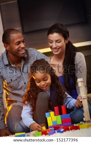 Happy interracial family sitting on floor at home, playing together, smiling. - stock photo