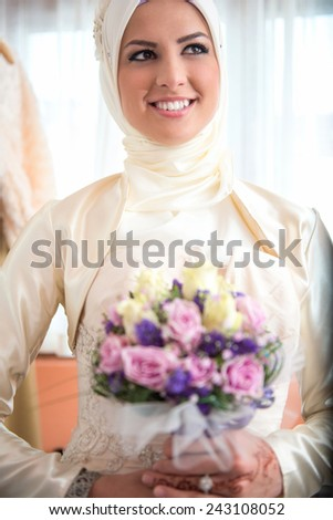 Happy islamic girl holding a bouquet of flowers - stock photo