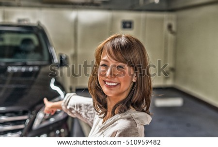 Happy japanese girl showing her brand new car.