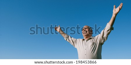 Happy joyful elderly man embracing the sun standing outdoors under a clear sunny blue sky with his arms outspread as he rejoices in nature, with copyspace