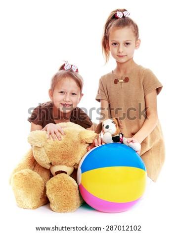 Happy joyful girls sisters playing favorite toys-Isolated on white background - stock photo