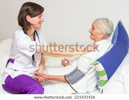 Happy joyful nurse caring for  an elderly woman  helping her days in nursing home.  - stock photo