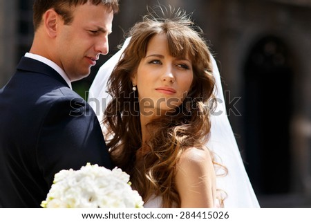 happy joyful young blond bride and groom on the background excellent sunny architecture