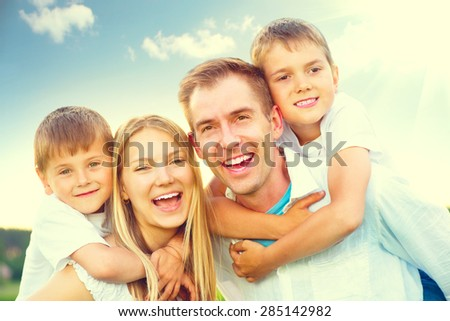 Happy joyful young family father, mother and kids having fun outdoors, playing together outside. Mom, Dad and kid laughing and hugging, enjoying nature. Sunny day, good mood
