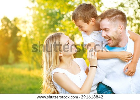 Happy joyful young family father, mother and little son having fun outdoors, playing together in summer park, countryside. Mom, Dad and kid laughing and hugging, enjoying nature outside. Piggyback - stock photo