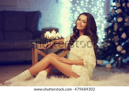 Happy joyous girl with long curly hair sitting on white fur carpet against bokeh lights, christmas tree and sofa