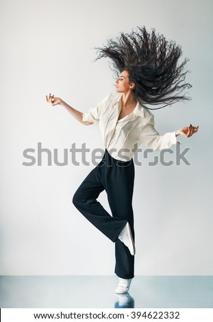 Happy jumping dancing girl with flying hair - stock photo