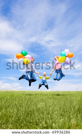 happy jumping family with balloons outdoor on a summer day - stock photo
