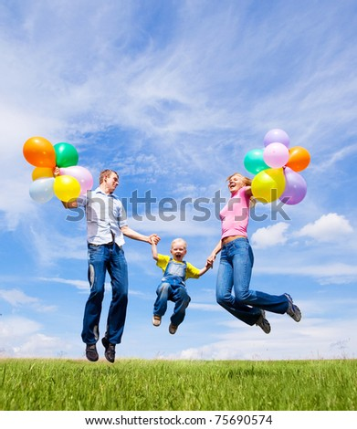 happy jumping family with balloons outdoor on a summer day