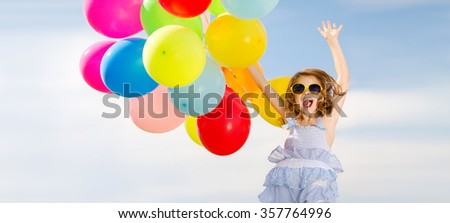 happy jumping girl with colorful balloons - stock photo