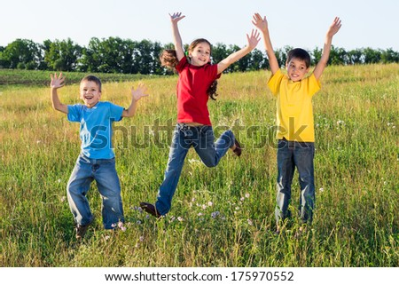 Happy jumping kids on green field, outdoors - stock photo