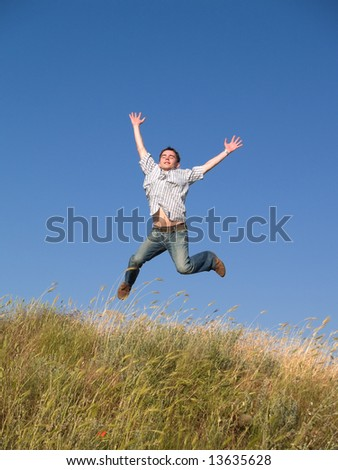 Happy jumping male teenager above green grass hill - stock photo