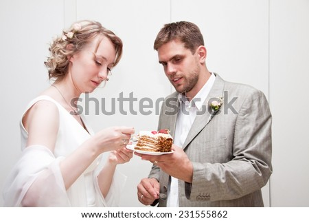 Happy just married couple eating wedding cake - stock photo