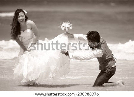 happy just married young couple celebrating and have fun at beautiful beach - stock photo