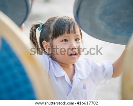 Happy kid, asian baby child in school uniform playing on playground