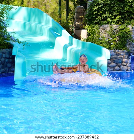 Happy kid, blonde caucasian boy, having fun floating and sliding in water park on inflatable ring enjoying sunny summer vacation in tropical resort - stock photo