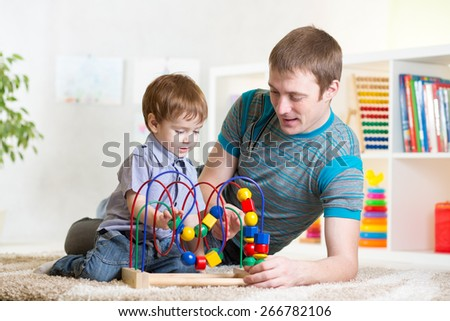 happy kid boy and dad playing toy together - stock photo