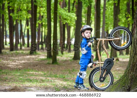 Happy kid boy of 4 years having fun in autumn or summer forest with a bicycle on beautiful fall or spring day. Active child making sports. Safety, sports, leisure with kids concept.